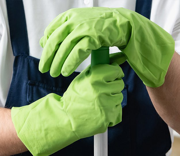 Cropped view of worker of cleaning service in rubber gloves holding mop in office