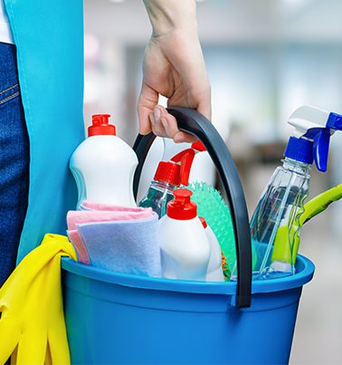 A cleaning woman is standing inside a building holding a blue bucket fulfilled with chemicals