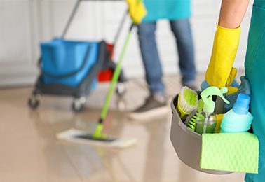 janitor with cleaning supplies in kitchen